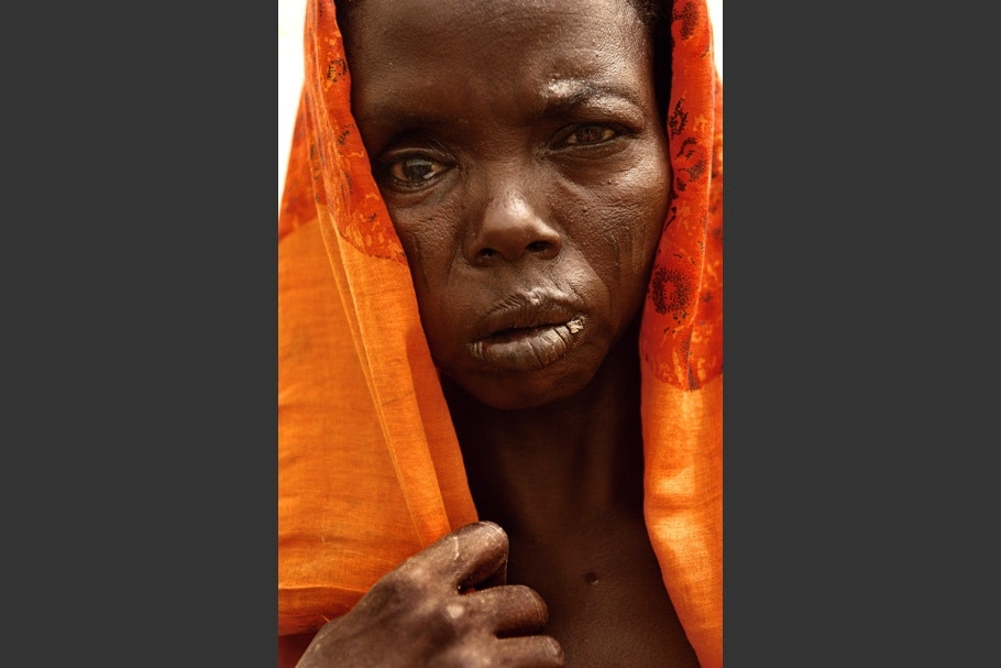 Woman with orange cloth covering her head.
