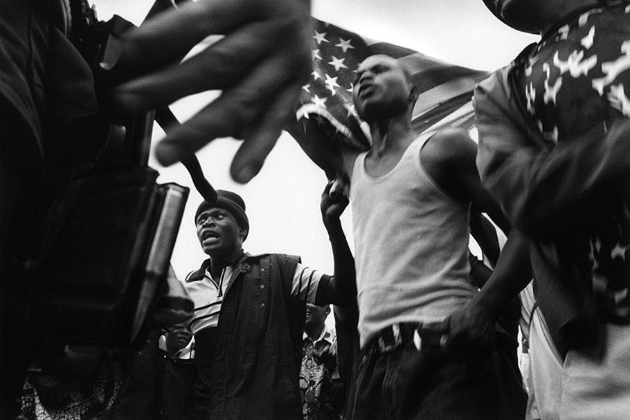 Men demonstrating under an American flag.