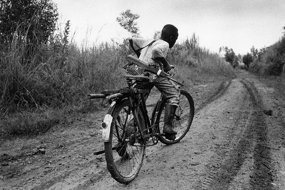 A child soldier on a bicycle.