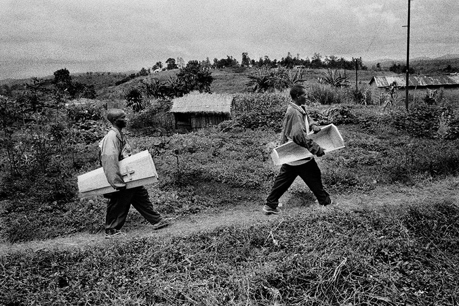 Two men carrying a child's coffin.