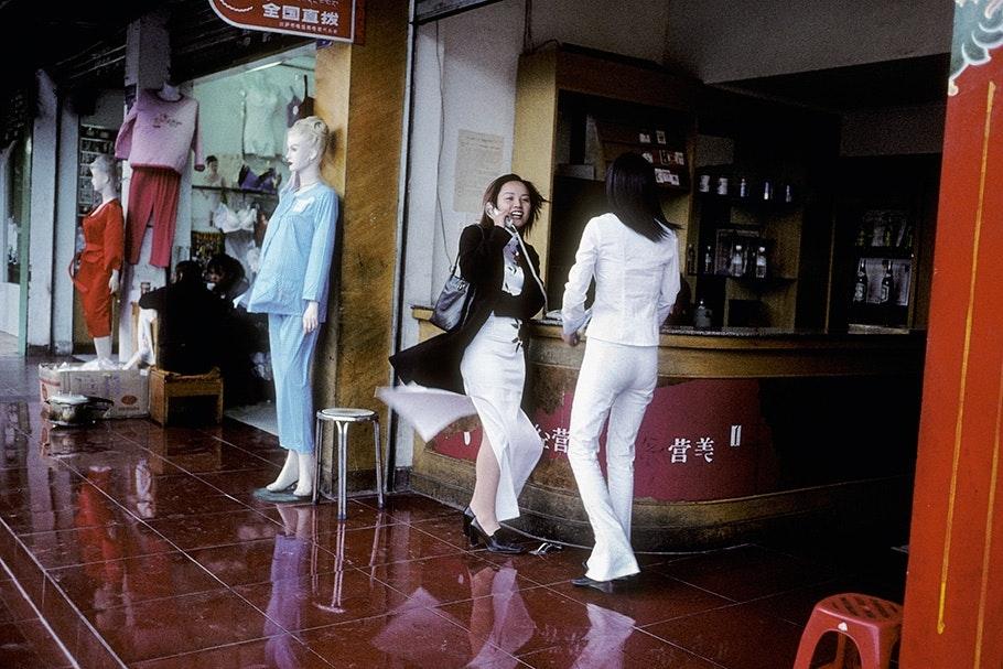 Women walking near mannequins.