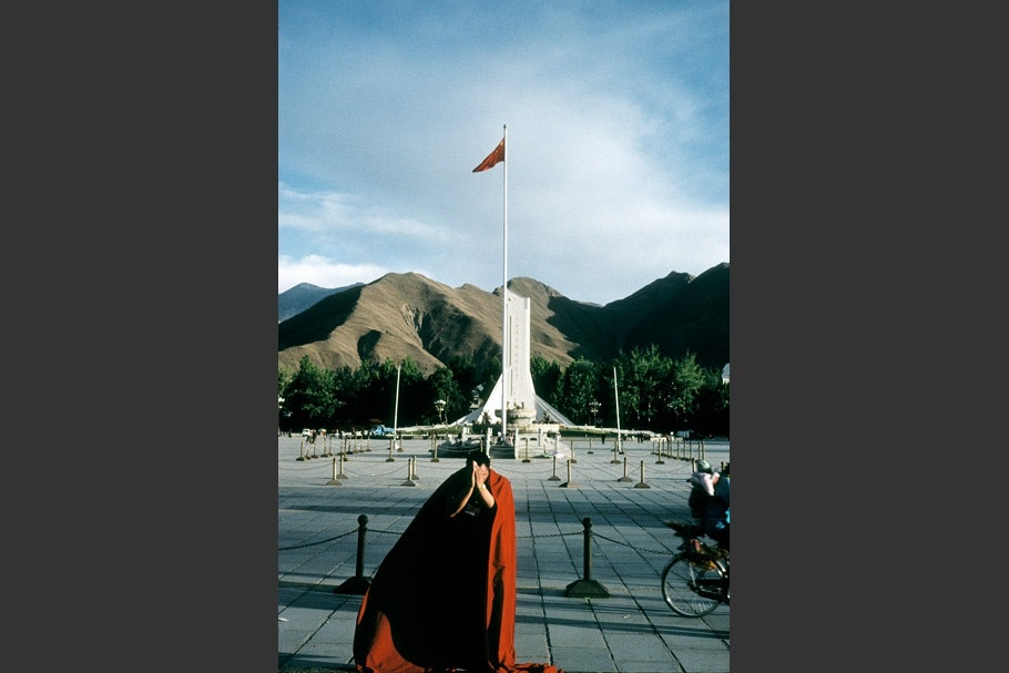 A monk in front of a flag.