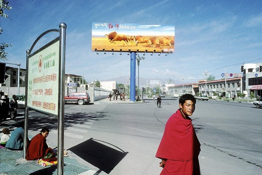 Man standing on sidewalk with billboard in background.