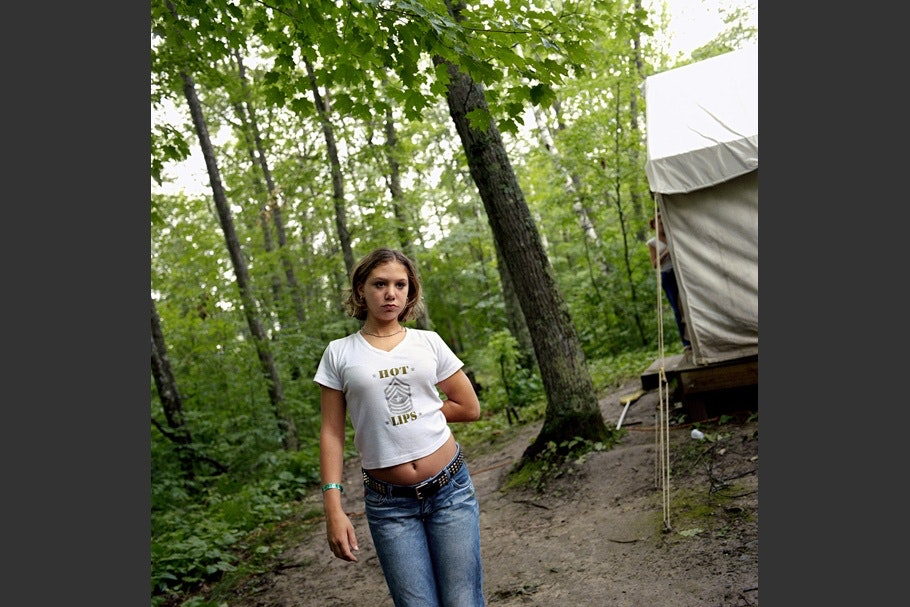 Teenage girl in jeans and a white t-shirt outside of a tent.