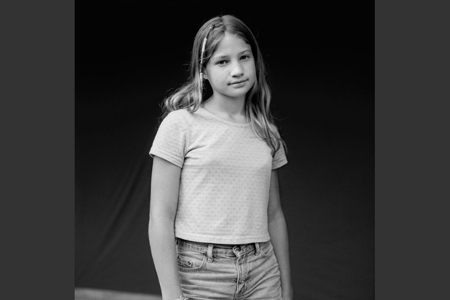 Black and white portrait of a girl in jeans with thread decorations in hair.