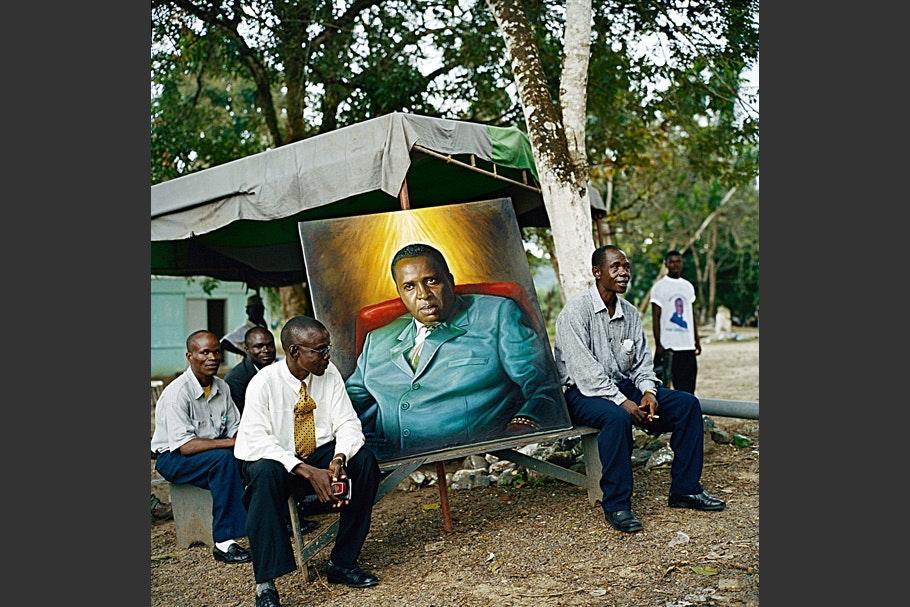 Men surrounding a painted portrait.