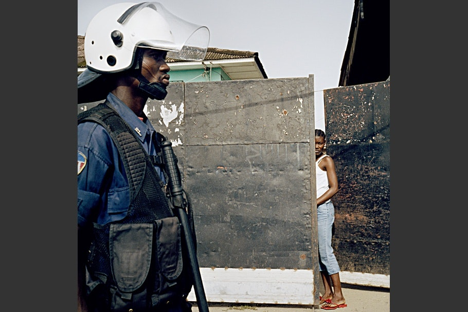 Policeman on a street with a woman in the background.