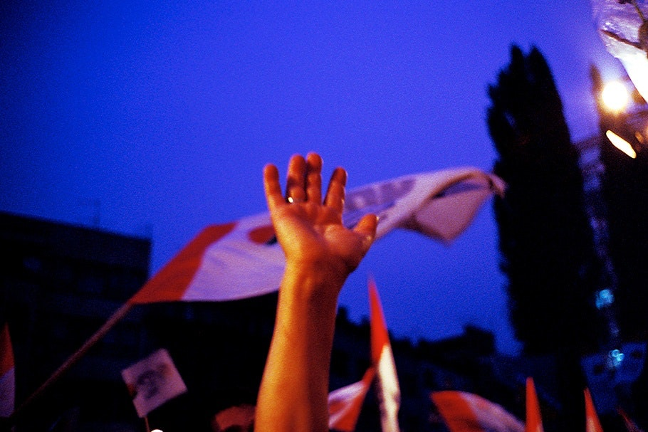 Hands and a flag against a night sky.