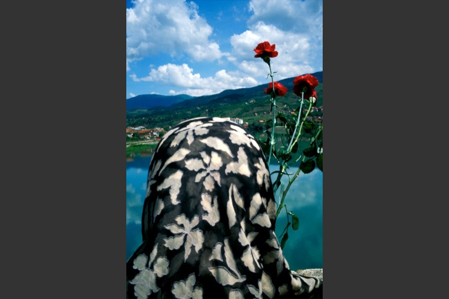 A woman in a headscarf viewed from behind, with flowers.