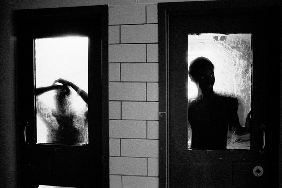 Two silhouetted figures seen through doors.