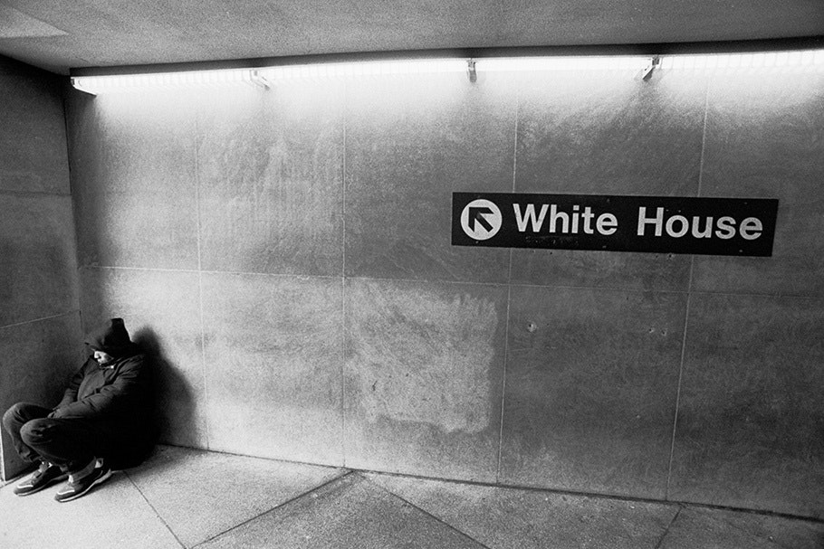"""A homeless man in a corridor with a """"White House"""" sign."""