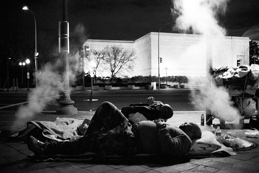 People sleeping in front of an illuminated building.