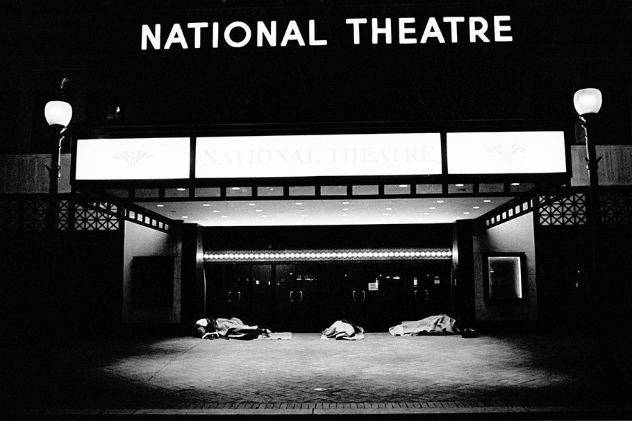 People sleeping under a theater marquee.