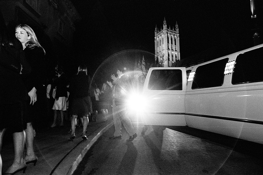 A group of teenagers outside of a limousine near the Cathedral.