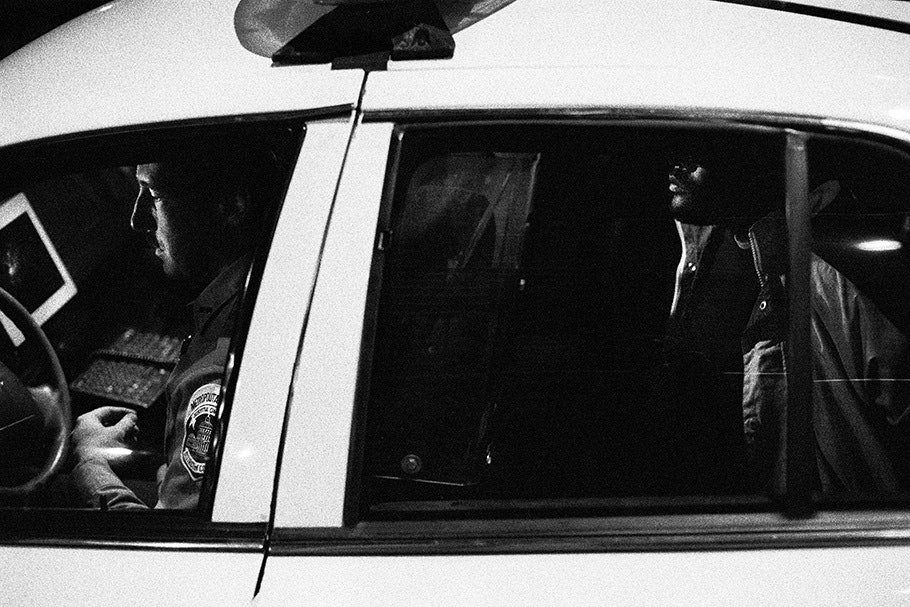 Officer and man seen through the side of a police car.