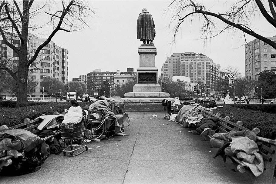 Homeless people in front of a statue.