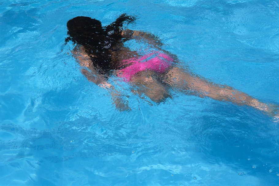 A child with an amputated leg swimming.