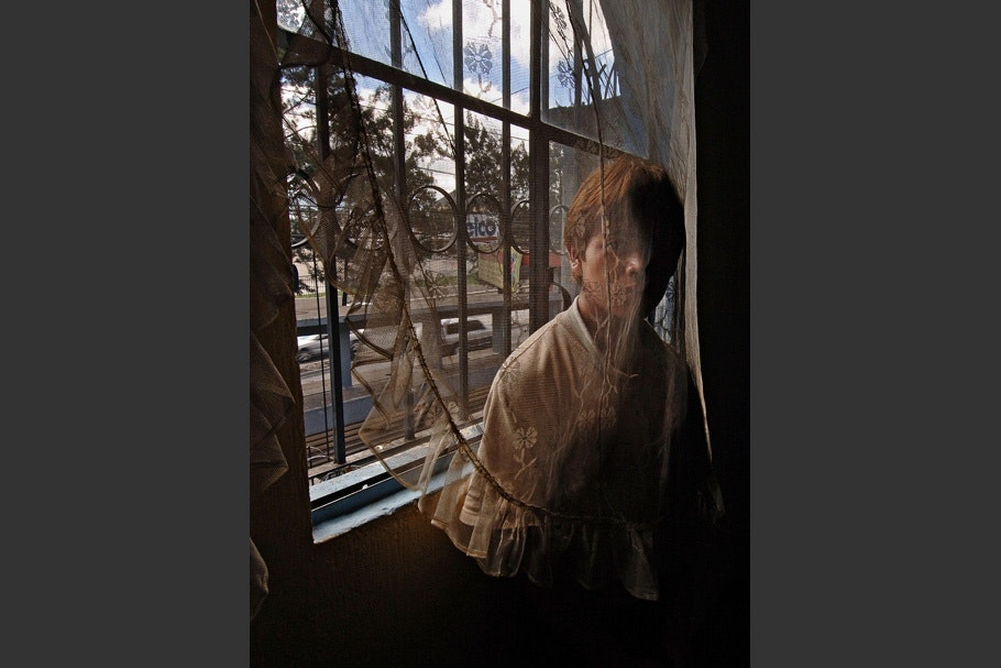 A teenager in a window behind a lace curtain.