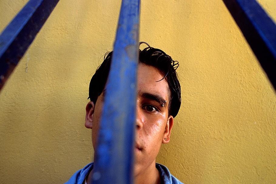 A teenage boy viewed through bars.