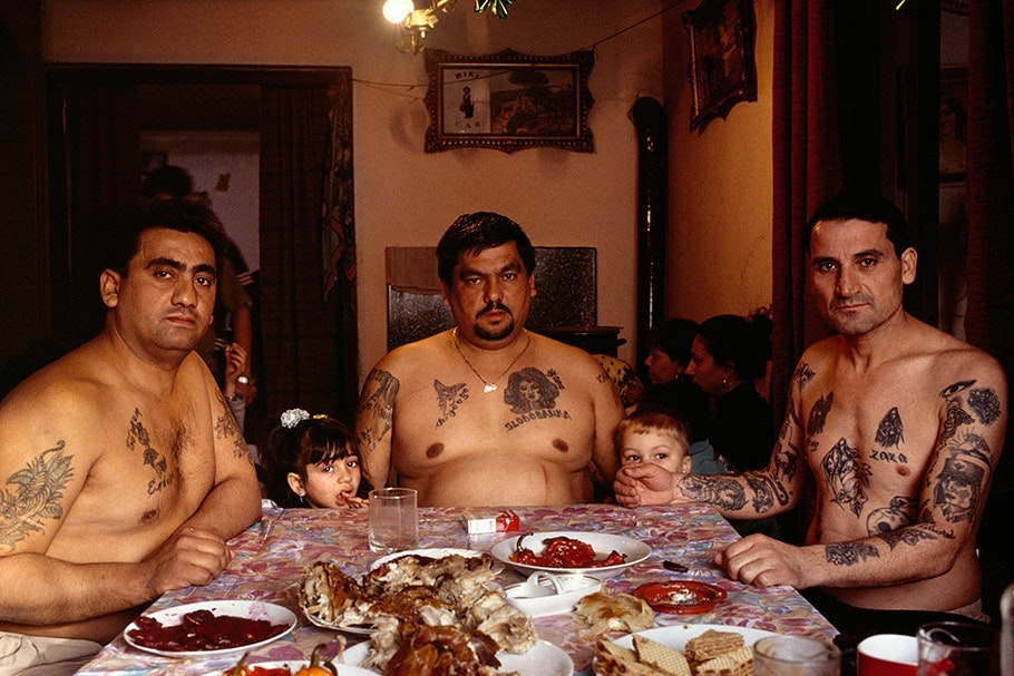 Three tattooed men and two children at a table.
