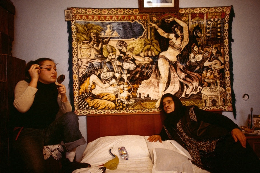 Two women in front of a tapestry.