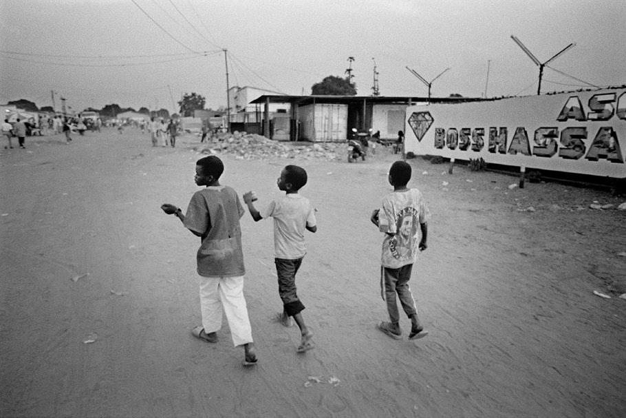 Three children walking in front of a diamond advertisement.