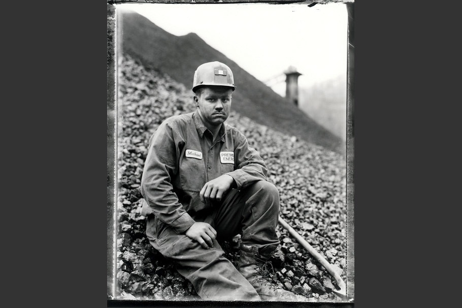A miner sitting on a hill wearing a hard hat.