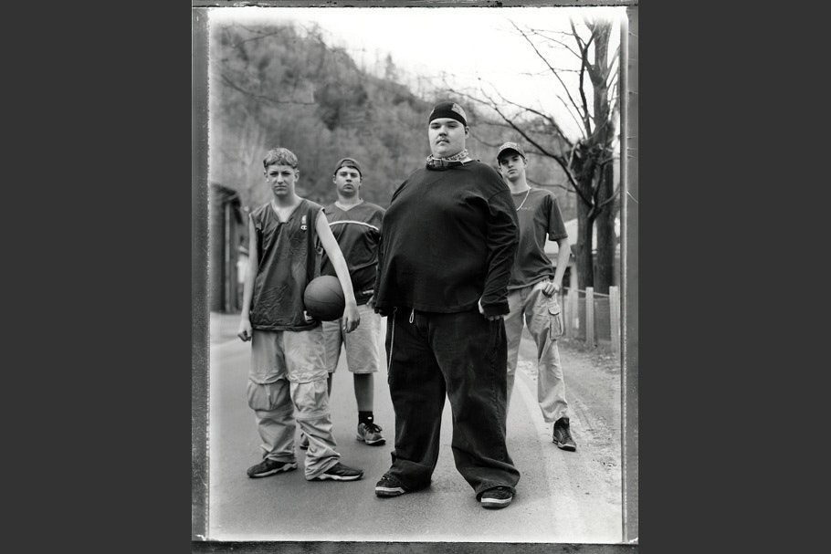 Four teenage boys standing in a road, one with a basketball.