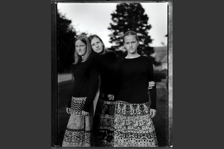 Three sisters in long patterned skirts.