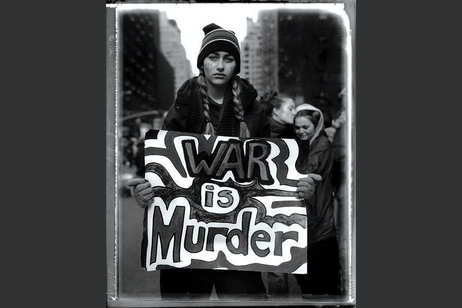 """Teenage girl carrying a """"War is murder"""" sign at antiwar protest."""