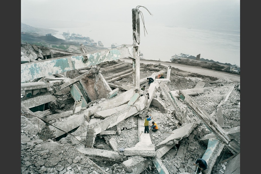 Buildings in the process of being destroyed, with construction workers.