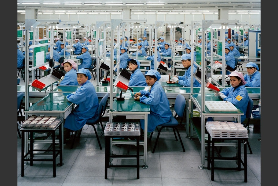 Factory workers in blue uniforms.