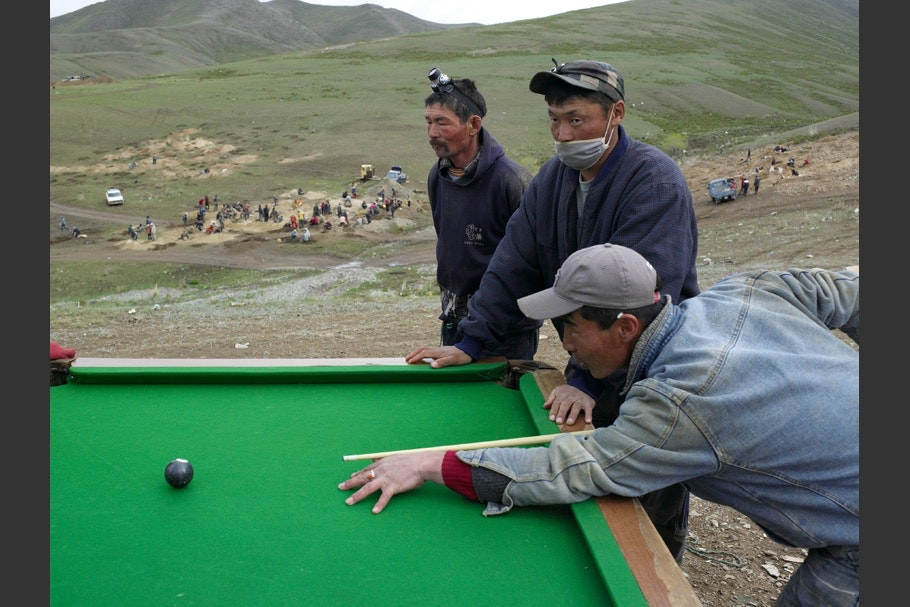 Men playing pool at an open air table.