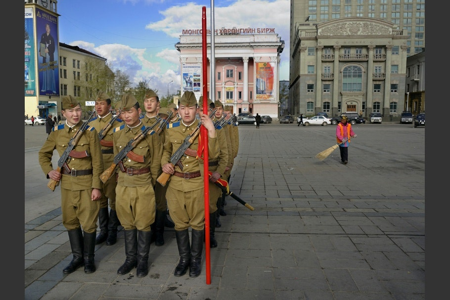 Soldiers standing in formation in a city square.