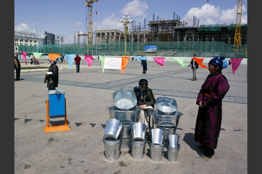 Women selling tin buckets under a string of flags.