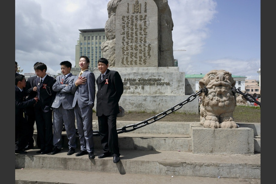 Boys in suits in front of a statue.
