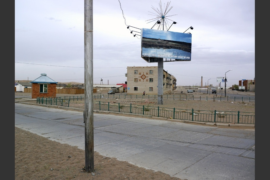 A billboard in front of an apartment building.