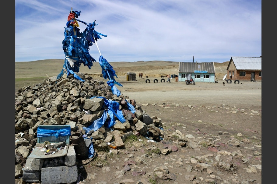 Tangle of blue prayer flags on top of a stone cairn.