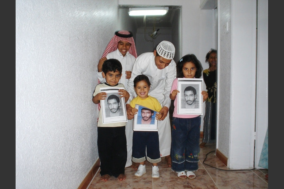 A family with children holding framed photographs.