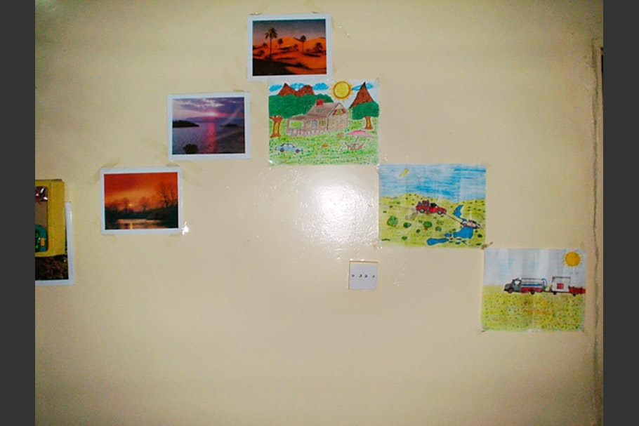 A wall with landscape photographs and children's drawings.