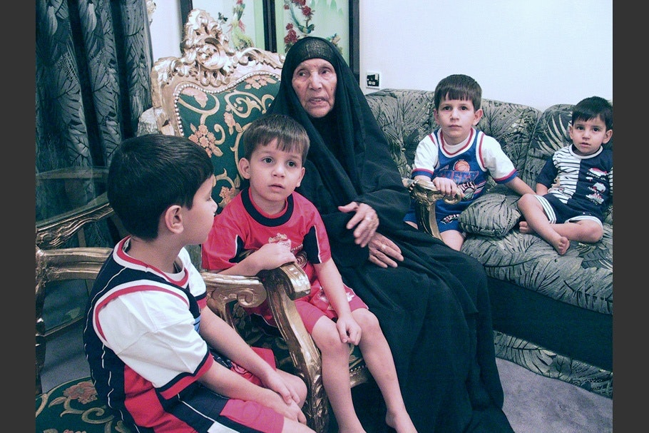 A woman wearing black with four boys.