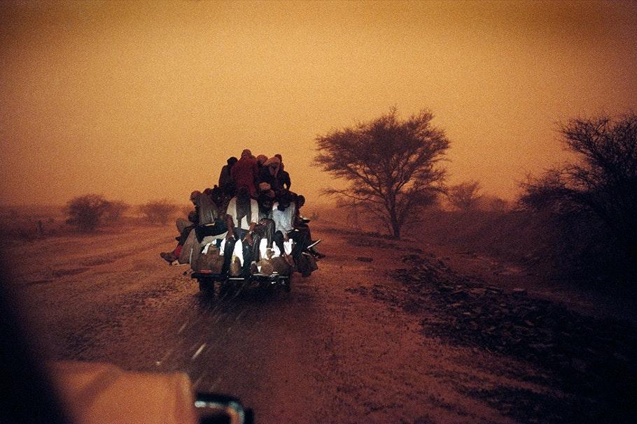A truck driving through the desert at night.
