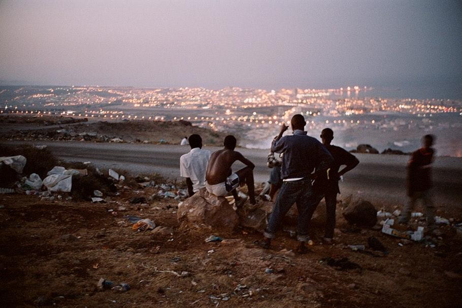 Men overlooking a city at dusk.