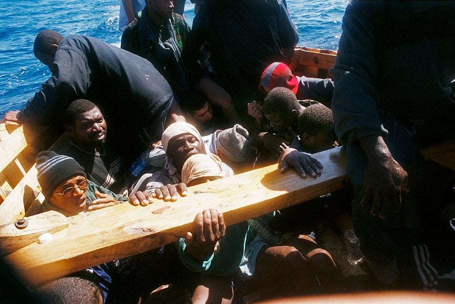 Men on a boat facing camera.
