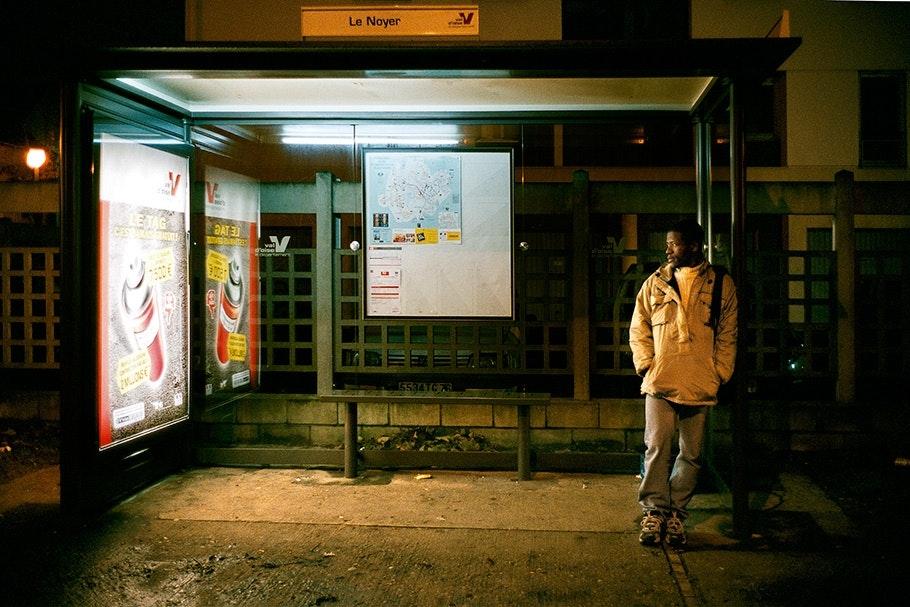 Man waiting at a bus shelter.