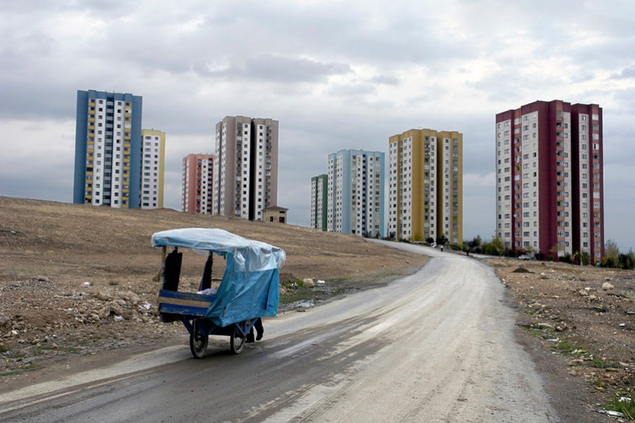 Apartment buildings and wagon with blue tarp.
