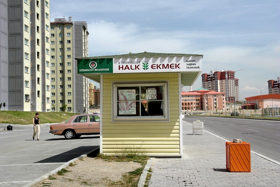 "Yellow booth (""Halk Ekmek"") in foreground, car and buildings in background."