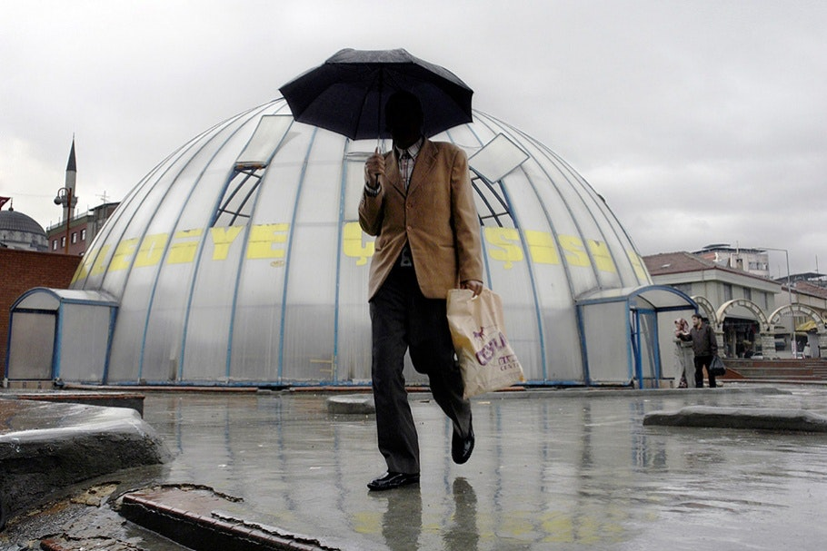 Man with umbrella in front of dome.
