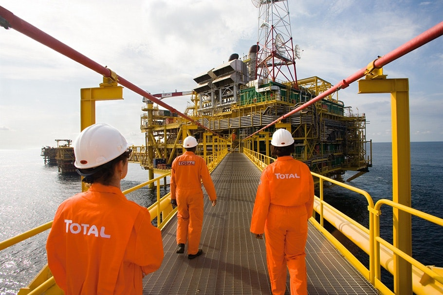 People in orange suits walking on oil rig walkway.