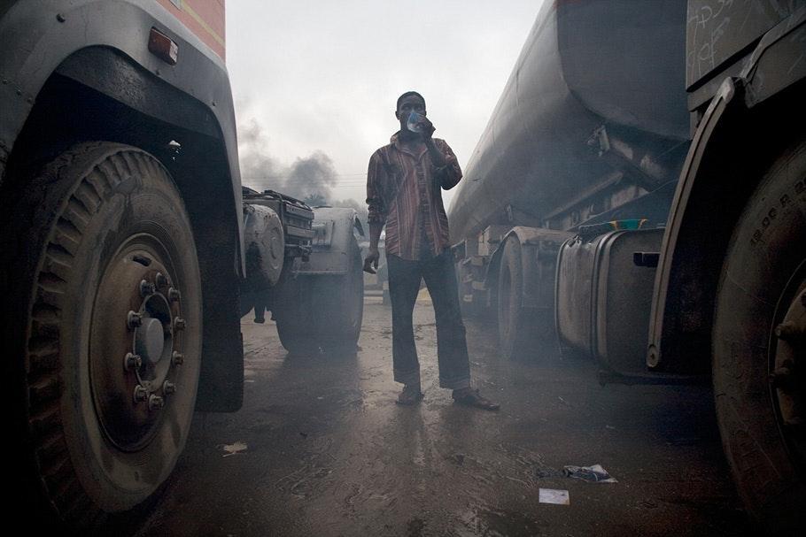 Man between trucks with smog.